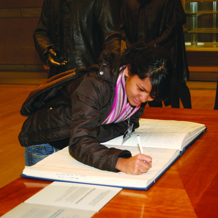 American Indian female student signing a book like founding father in Philadelphia