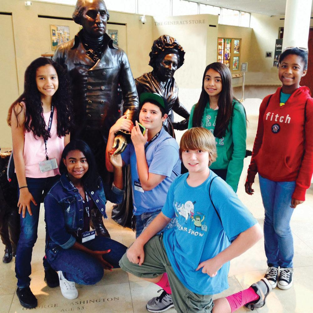 Middle school students posing with a statue of George Washington at Mount Vernon